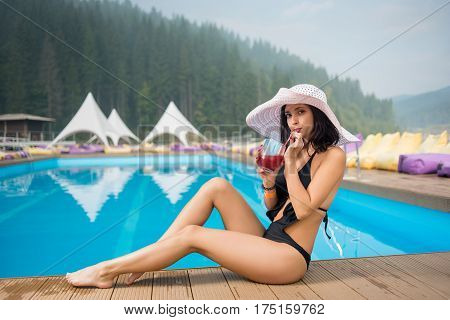 Young Beautiful Female In A Hat And Black Bikini Sitting Next To Swimming Pool, Drinking Cocktail An