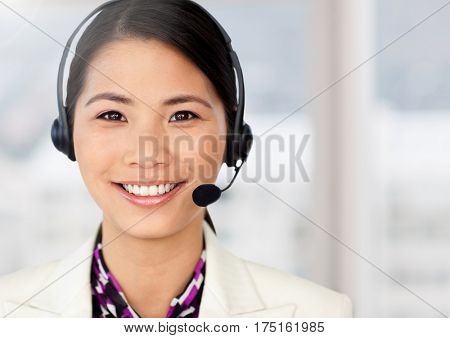 Smiling woman wearing headphones at office