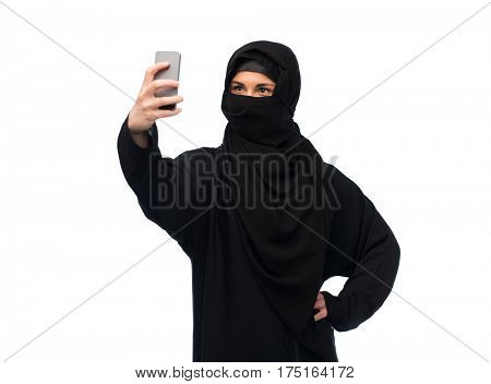 technology and people concept - muslim woman in hijab taking selfie with smartphone over white background