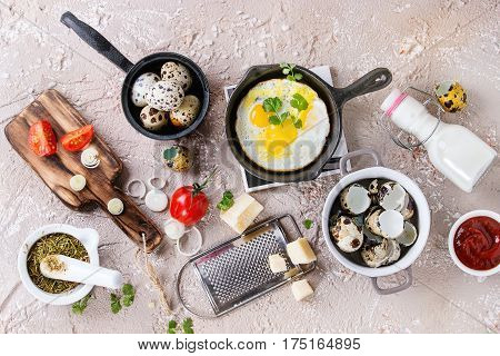 Breakfast with fried quail eggs in iron cast pan, cherry tomatoes, onion, ketchup sauce, seasonings in mortar, cheese grater, egg shell in pot. Beige concrete texture background. Top view with space.