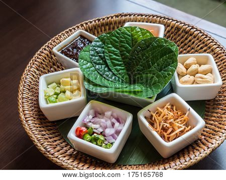 A royal leaf wrapped appetizer, one bite of food wrapped in green leaves