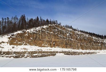 Cliff of sandstone in winter on the Chulman River in South Yakutia Russia