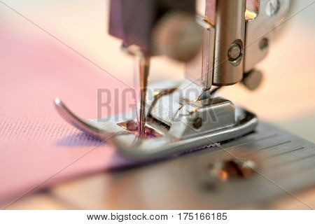 needlework and tailoring concept - sewing machine presser foot stitching fabric poster
