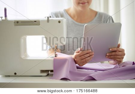 people, needlework, technology and tailoring concept - tailor woman with sewing machine, tablet pc and fabric