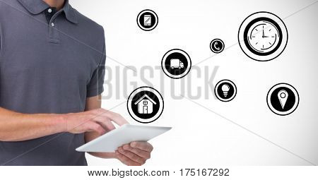 Digital composition of man using digital tablet with various icons in background