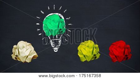 Digital composition of crumbled paper on drawn light bulb in black background