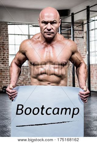 Portrait of bodybuilder holding placard with text bootcamp in gym