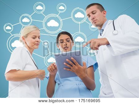 Digital composition of male and female doctors discussing over digital tablet with cloud computing icons in background