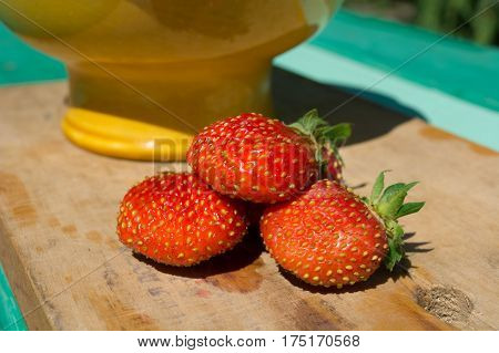 Strawberry berries on a wooden board. Earlier morning in the summer in a garden.
