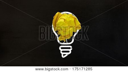Conceptual image of idea with light bulb and crumpled paper against black background