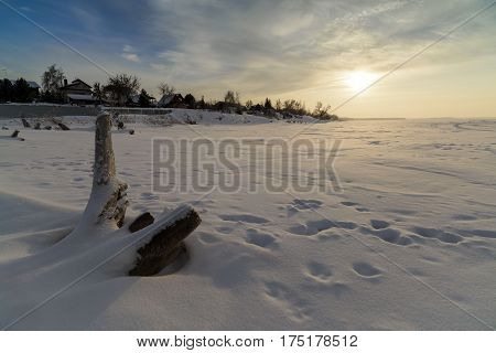 Winter landscape with a view of the setting sun over the frozen sea