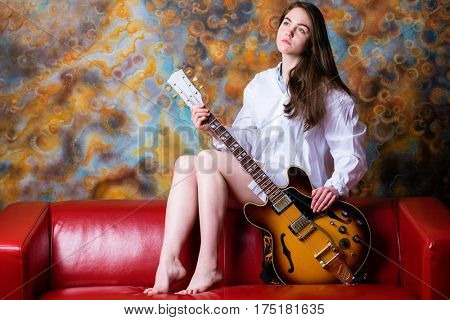 Podolsk, Russia - February 21, 2017: Young brunette girl with a vintage electric guitar Gibson es-345 1969 model year