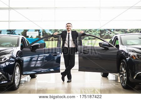 Confident smiling car salesman at the showroom he is standing near open cars doors of luxury cars