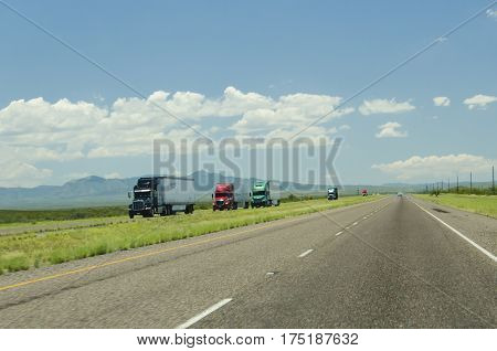 A highway in New Mexico, packed with many truck trailers.