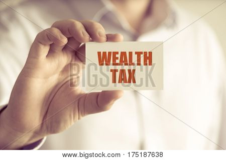 Businessman Holding Wealth Tax Message Card