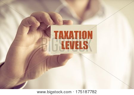 Businessman Holding Taxation Levels Message Card