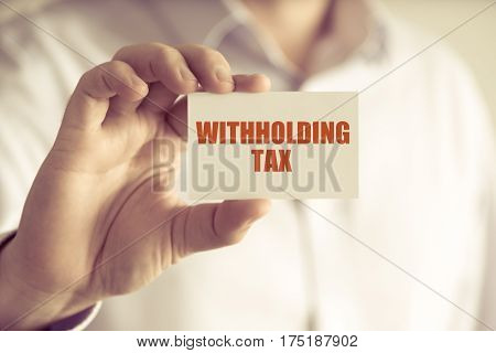 Businessman Holding Withholding Tax Message Card