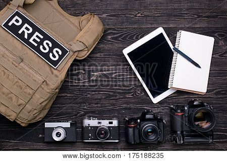 Bulletproof vest,retro and professional DSLR camera,notebook,pen and PC tablet on dark wooden table.Top view