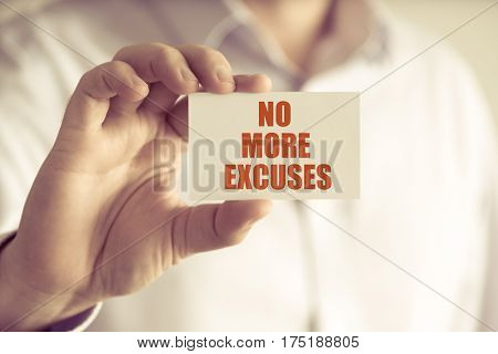 Businessman Holding No More Excuses Message Card