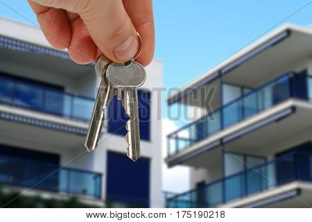 Keys in hand for apartment over blue sky.