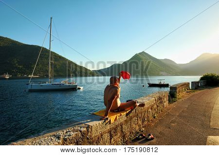 PERAST, MONTENEGRO - JULY 14, 2016: a man in a swimsuit is sunbathing along the road is protecting themselves from the light of the sun setting with a red cap