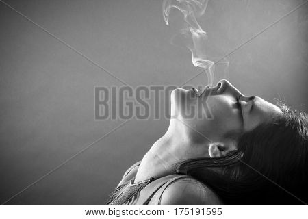 Smoking, Brunette woman with smoke coming out of her lips, concept smoker and tobacco