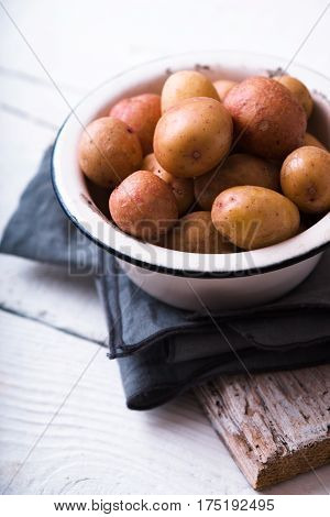 Raw potatoes in a white bowl on a napkin vertical
