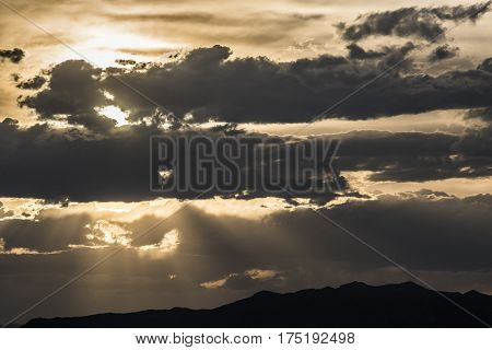 Dramatic yellow cloudy sunset with sun rays and mountains at Bonneville white salt flats, Utah