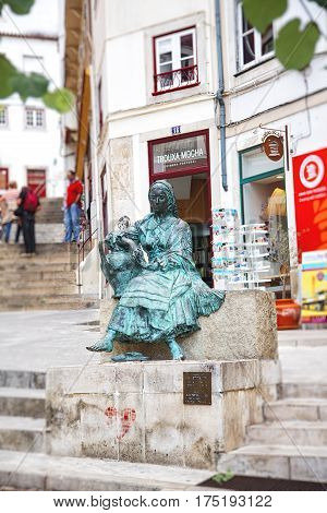 COIMBRA PORTUGAL - September 26 2013: Monument to the singers of the old town the Tricana of Coimbra in the Almedina district of Coimbra. The most popular sculpture of Coimbra is also called Girl with a jug.