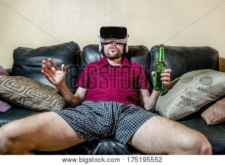 The man in glasses virtual reality plays on the black sofa at home with a bottle of beer