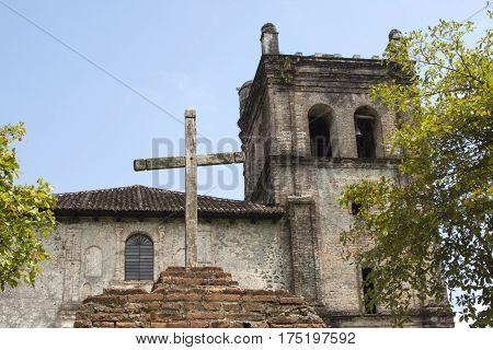 Wooden cross in front of rustic Nuestra Senora de la Asuncion Catholic Dominican convent church founded in 1590 in Chapultenango Chiapas Mexico