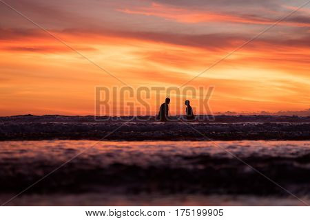 Silhouette of a couple at the beach during a fiery orange sunset. - Seminyak Beach, Bali, Indonesia.