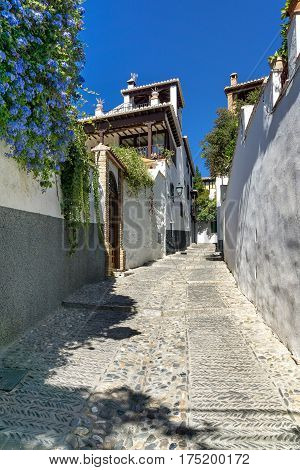 An alley in Granada. Architecture and flowers: An alley in the Arab city quarter Albaicin in Granada.