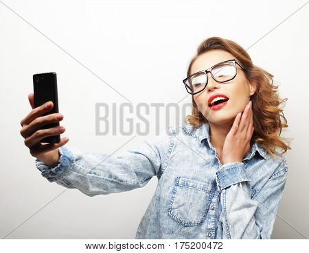 life style, happiness, emotional and people concept: Pretty hipster girl taking selfie.