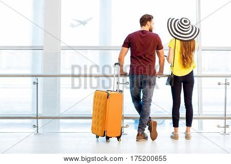 Young couple in colorful t-shirts waiting with baggage near the window at the departure area of the airport during their summer vacation