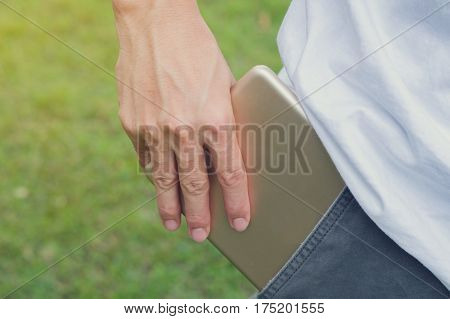 Close up of a hand of a businessman holding a tablet computer, abstract holding a tablet with out of pocket in nature background