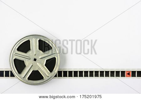 Metal reel with film on white background
