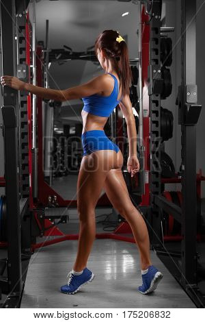 Beautiful sexy girl with perfect buttocks at the gym. The concept of a healthy lifestyle and exercise. Strong woman. Feminism.