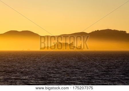 Beautiful view of famous Alcatraz Island illuminated in majestic golden evening light at sunset in summer San Francisco Bay California USA