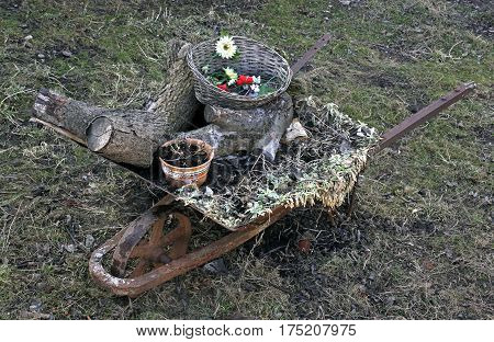 Wheelbarrow with household rubbish weeds and firewood