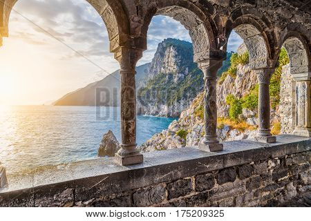 Columns of famous gothic Church of St. Peter (Chiesa di San Pietro) with beautiful shoreline scenery at sunset in the town of Porto Venere Ligurian Coast province of La Spezia Italy