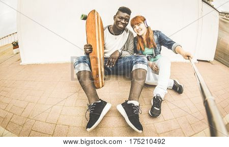 Multiracial couple in love taking selfie having fun together outdoors - Relationship concept with trendy people on urban fashion style - Redhair girl with african american guy - Retro vintage filter