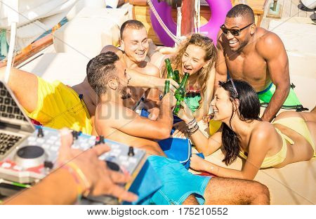 Group of multiracial friends having fun drinking at sail boat party with dj set - Friendship concept with young multi racial people toasting beer on sailboat - Travel lifestyle on warm vivid filter