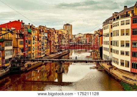 a view of the Onyar River as it passes through Girona, in Spain, some of its characteristics colorful houses and bridges, highlighting the red one built by Eiffel, and the Old Town on the left