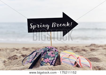 closeup of a black signboard in the shape of an arrow sign with the text spring break written in it and two pairs of colorful flip-flops on the sand of a lonely beach