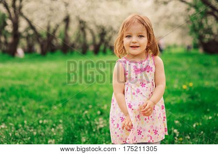 cute little happy toddler girl portrait walking in spring or summer park or garden