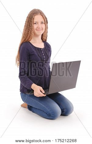 Student teenage girl sitting sideways on the floor with laptop isolated on white