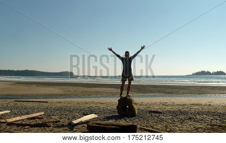 Women at the beach standing on a big piece of driftwood lifting her arms up in front of the sea feeling freedom