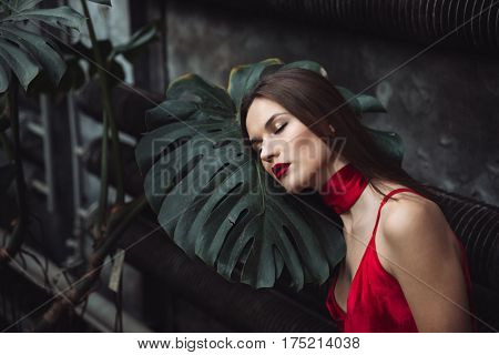 Model in red dress which posing with closed eyes near the plant in greenhouse