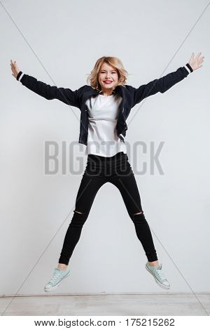Full length portrait of a joyful young woman jumping over white background